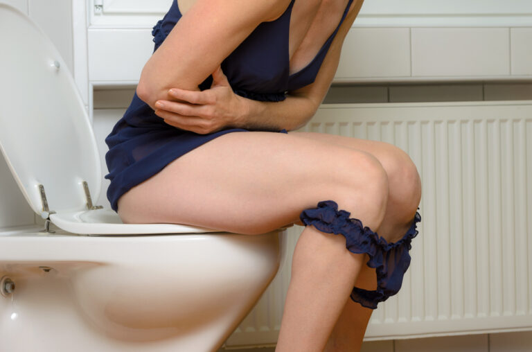Sitting on the toilet.
